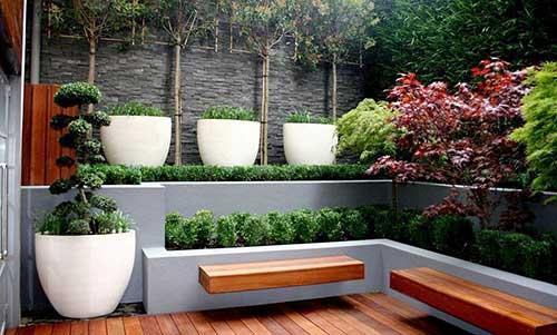 banco de madeira colado na parede em jardim de inverno