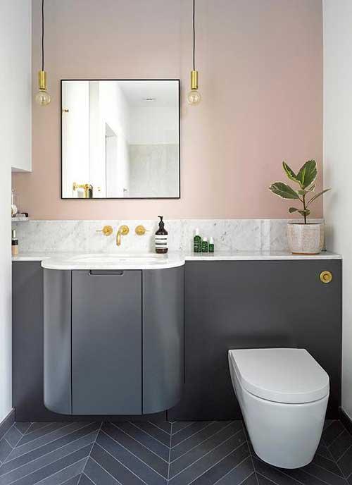 banheiro rosa e cinza com objetos dourados