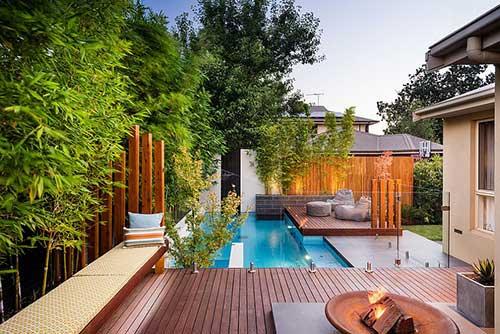jardim com piscina com deck de madeira e plantas