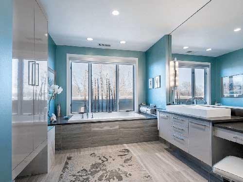 banheiro cinza e azul claro com banheira aquecida