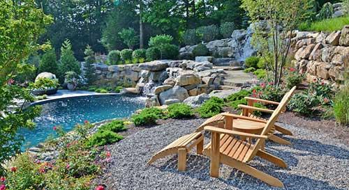 area de lazer grande com piscina, plantas e cadeiras de madeira