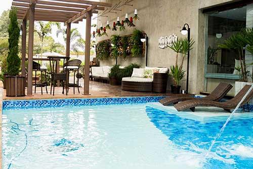 quintal decorado com pergolado em piso de madeira e piscina de ceramica azul e verde