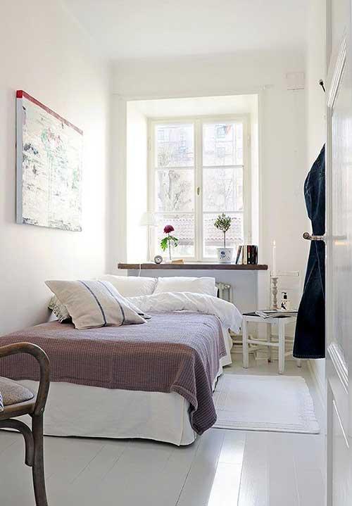 cama encostada na parede em quarto de casal branco em apartamento pequeno