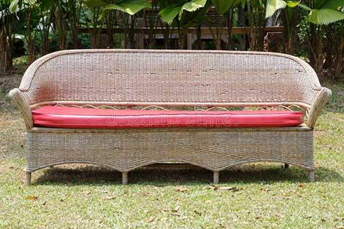 banco com almofada vermelho feito de vime pra ser colocado na grama do jardim