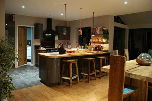 cozinha americana conjugada a sala de estar com moveis em madeira de demolição