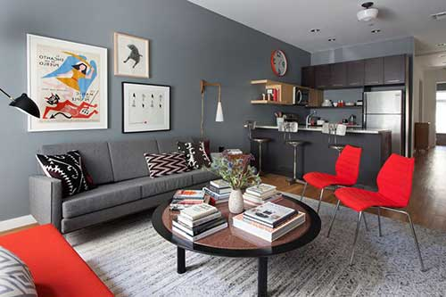 cozinha americana cinza integrada com a sala de estar enfeitada com cadeiras vermelhas