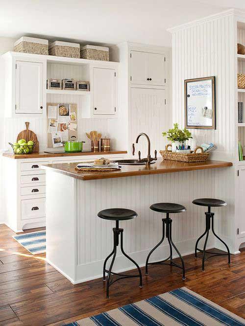 foto de cozinha americana junto com a sala de estar com madeira pintada de branco