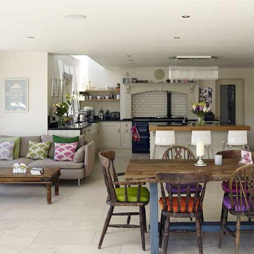 cozinha americana com mesa de jantar rustica e almofadas coloridas