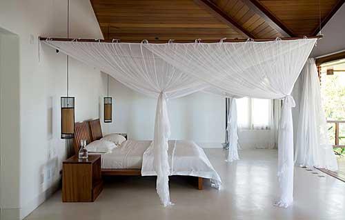casa de praia decorada com dossel, moveis de madeira e piso vinilico liso