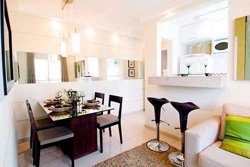 cozinha americana integrada com sala de estar e de jantar em apartamento pequeno