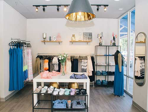 loja pequena feminina com decoracao clean e piso laminado