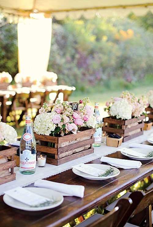 mesa de banquete de casamento ornamentada com caixas de madeira