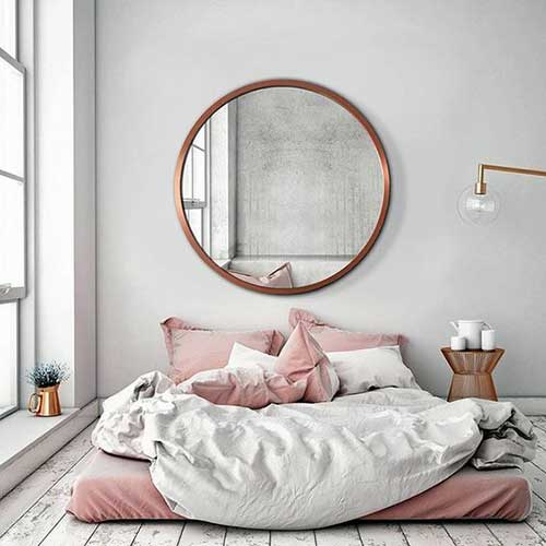 quarto com espelho redondo e cama de chao