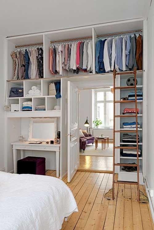 quarto branco com piso de madeira e armarios sem porta