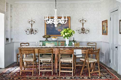 imagem de sala de jantar com paredes brancas e mobilia envelhecida