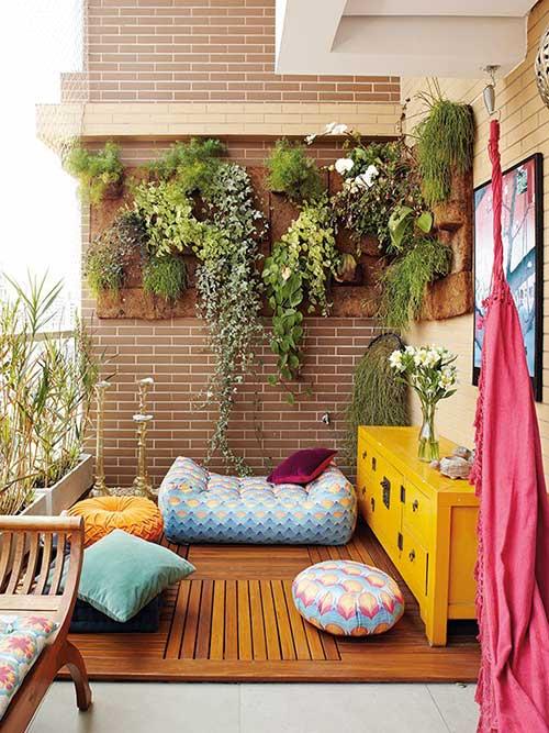 terraço pequeno com jardim vertical e deck de madeira