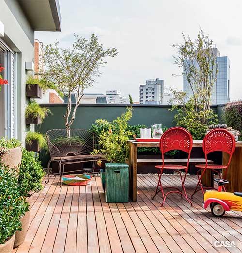 terraço com deck de madeira e cadeiras coloridas