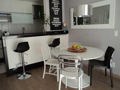 sala de jantar com mesa redonda com cadeiras diferentes para uma decoracao moderna
