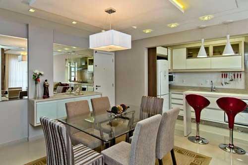 cozinha americana planejada completa com bancada, banquetas e mesa de jantar