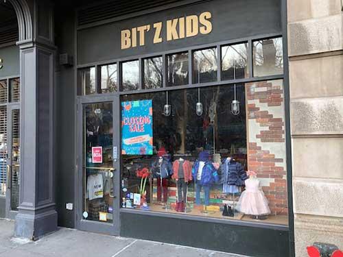 fachada preta de loja de roupas pra criança