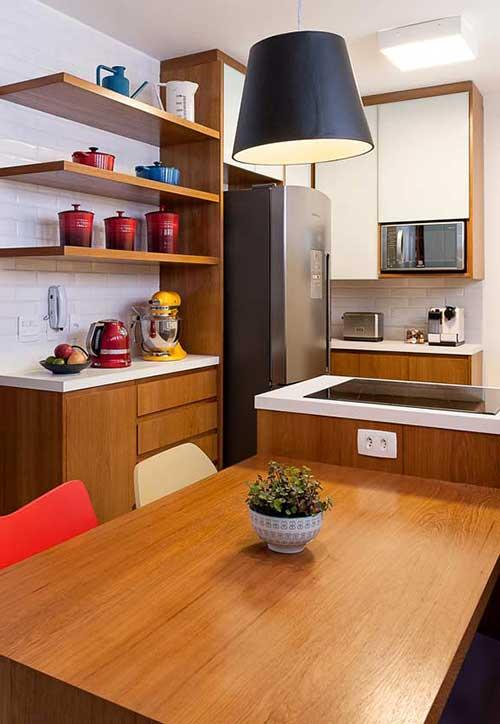 cozinha americana planejada com iluminaçao dirigida e cadeiras coloridas