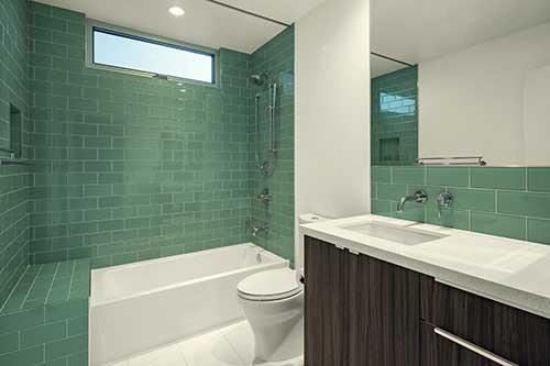banheiro branco com revestimento em pastilha de vidro verde