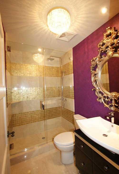 imagem de banheiro com box dourado e parede rosa