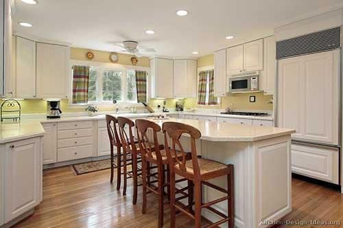 cozinha com parede amarela e cadeiras de madeira