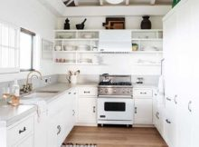 cozinha toda branca com nichos e teto de madeira