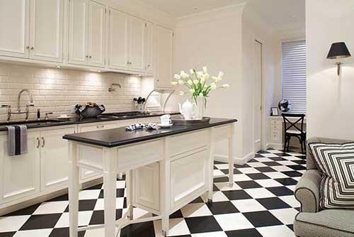cozinha preta e branca com piso quadriculado