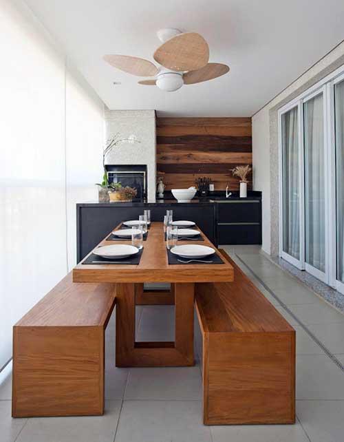 varanda gourmet de luxo com mesa de jantar e ventilador