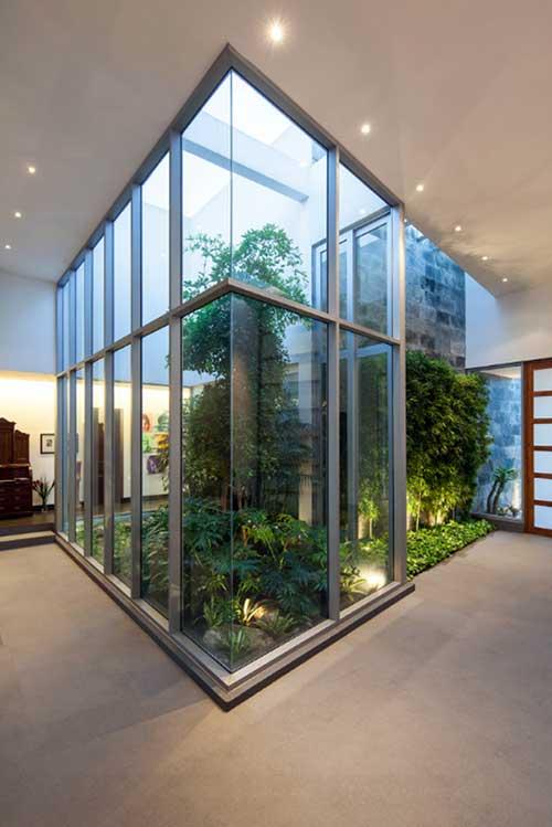 sala de estar com jardim de inverno e janelas de vidro