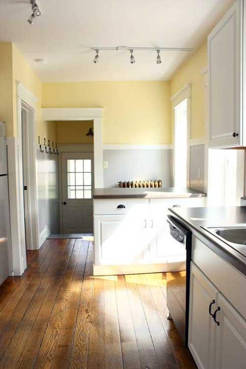 cozinha simples com parede amarela clara e cinza e piso de madeira