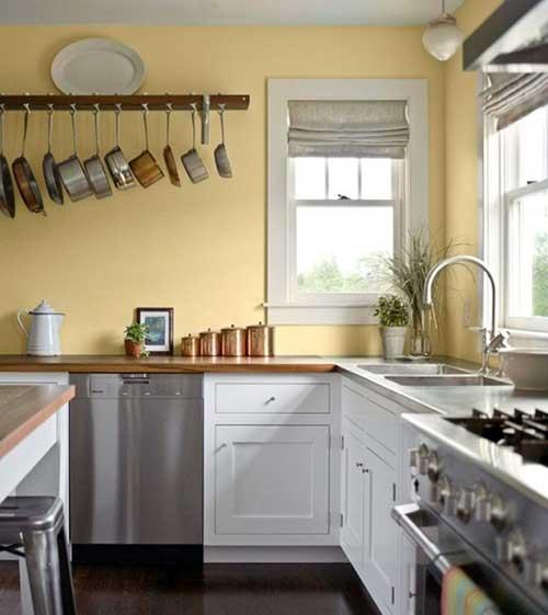 cozinha rustica com parede amarela, balcao de madeira e armario branco