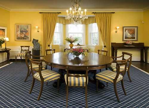 sala de jantar com paredes e cortinas amarelas e tapete azul