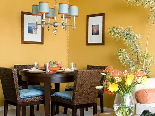 sala de jantar pequena com parede amarela e mesa para quatro pessoas marrom