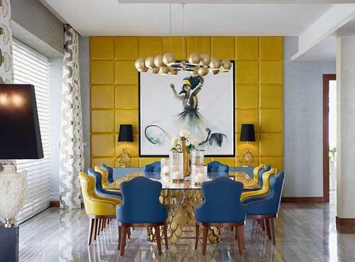 sala de jantar grande com parede amarela e cadeiras azuis