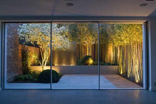jardim de inverno iluminado e visto da sala de estar