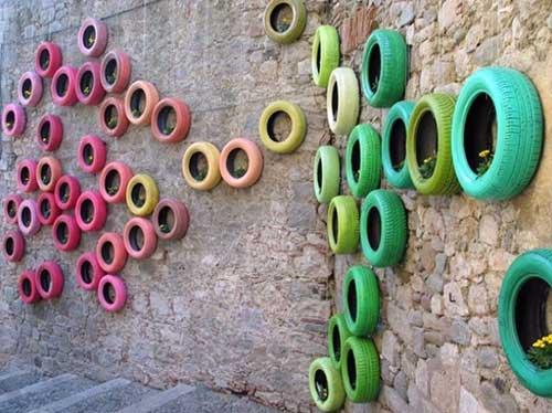 muro decorado com pneu colorido e plantas