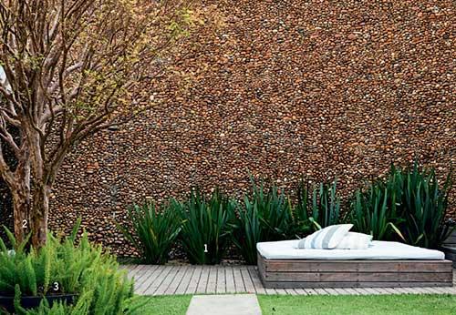 imagem de quintal com muro de seixos