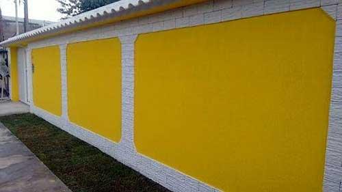 muro decorado com grafiato amarelo e pedras