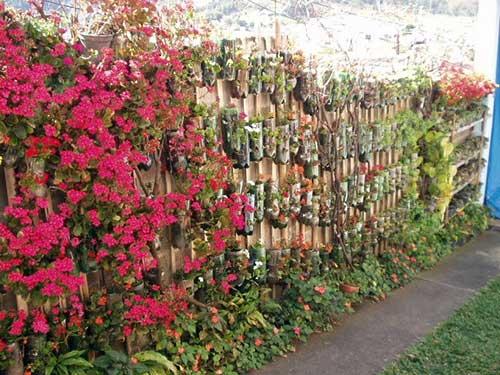 muro decorado barato com ripas de bambu e jardim de garrafas pet