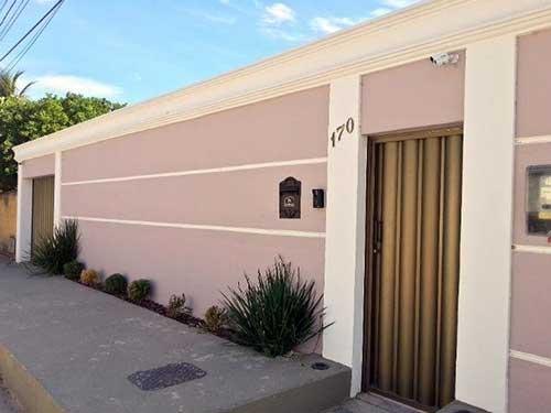 muro externo de casa em cor clara com friso branco