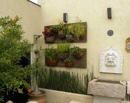 muro com jardim suspenso e painel de madeira