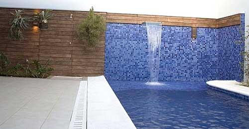 quintal com piscina com muro de pastilhas e madeira