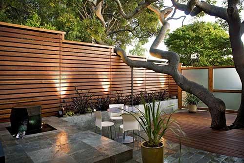 quintal de casa com muro decorado em madeira, plantas e arvore