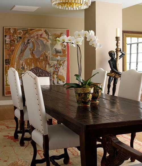 sala de jantar com mesa escura e orquideas brancas