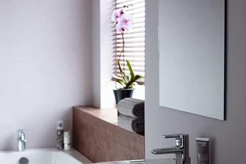 banheiro com pequena orquidea na janela