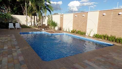 imagem de quintal com piscina e muro decorado com porcelanato