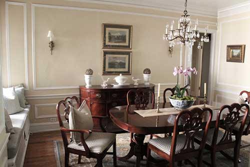 sala de jantar rustica com vaso de orquideas sobre a mesa